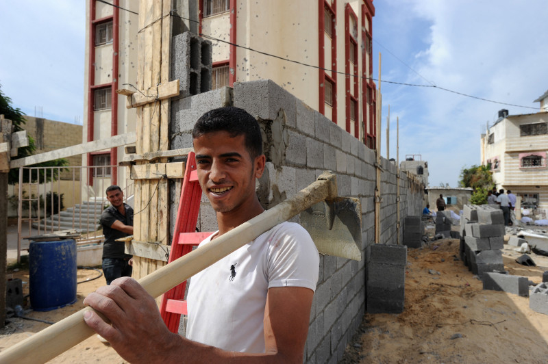 A cash-for-work project employs dozens of people to help rebuild and restore a destroyed kindergarten. This allows people within the community to earn wages as laborers. Photo by Shareef Sarhan for CRS
