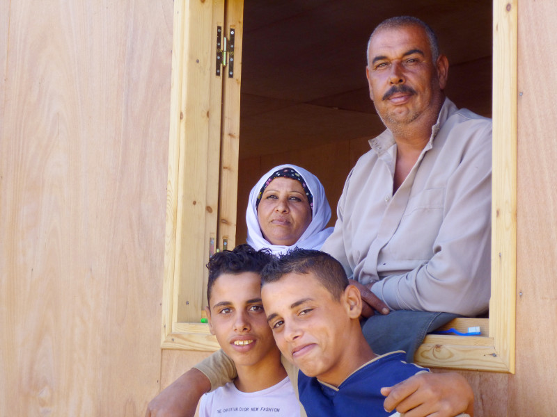 """We felt that we were not forgotten,"" says Abu Hussein, with his wife and their sons at a window in their new home, provided by CRS. Photo by Caroline Brennan/CRS"