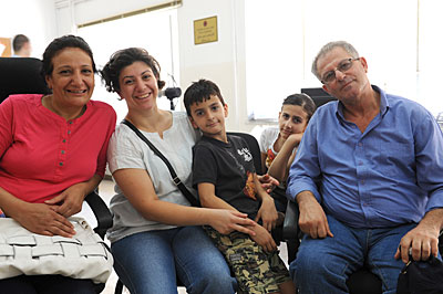 """We are lucky to just be with each other,\"" says Debo Issa Turk, far right, sitting at the Caritas Clinic near Amman, Jordan, with his family, Syrian Christians: from left to right, his wife, Salam Zekkar, their daughter Suna, and Suna's son Bashara."
