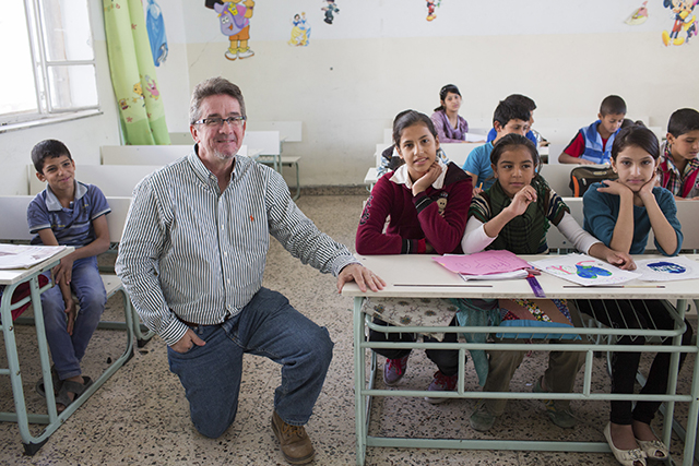 immy Patterson with Syrian refugee children in their classroom at the Latin School in Jordan. Photo by Andrew McConnell for CRS
