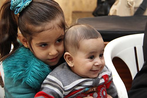 """Rawan, 5—playing with her baby brother, Ahmad—attends a CRS-supported preschool for Syrian refugee children in Jordan. Her mother says the school has made her \""""stronger.\"""" Photo by Kim Pozniak/CRS"""