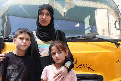 Ashaa, her son Jara and daughter Waed, with the bus they'll ride home after participating in CRS and Caritas educational programming in Zarqa, Jordan. Photo by Nikki Gamer/CRS