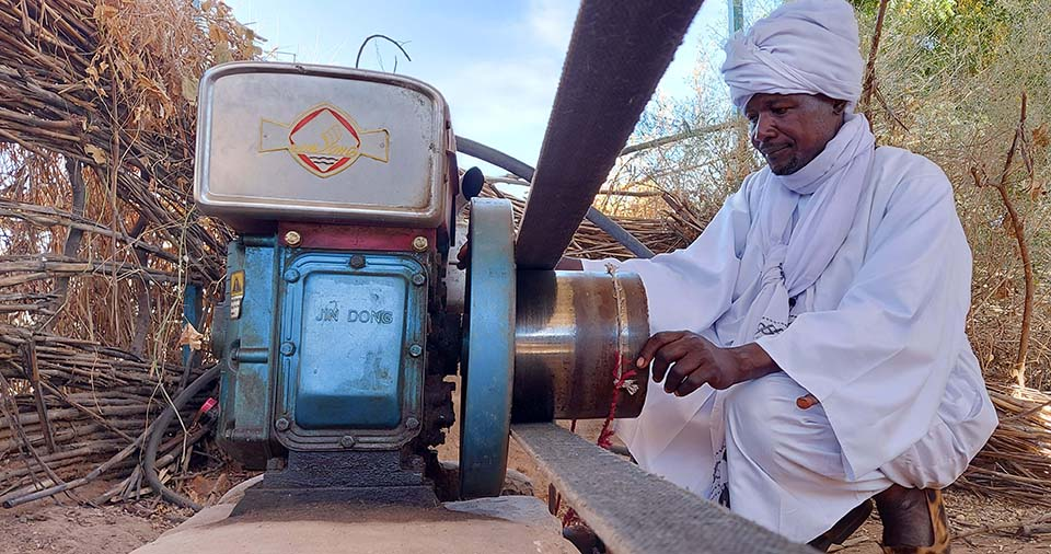 Sudanese savings group leader checks grinding mill operations