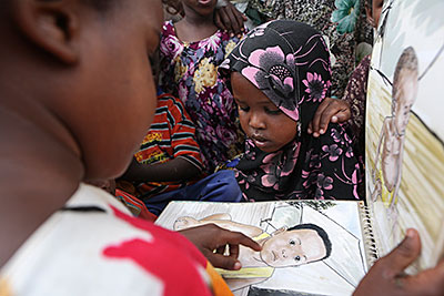 Farhiya points to pictures in a hygiene book given to her father by CRS. Photo by Sara A. Fajardo/CRS