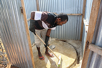 Hygiene promoter Ahmed Hussein disinfects his family's latrine in the world's largest refugee camp: Kambioos in Dadaab, Kenya. Photo by Sara A. Fajardo/CRS