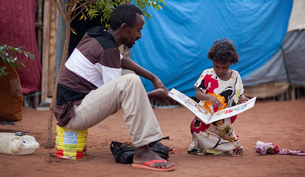 Ahmed Hussein and his daughter study a book on hygiene and sanitation outside their shelter at the Kambioos refugee camp in Kenya, where they sought refuge from the famine in Somalia. Photo by Sara A. Fajardo/CRS