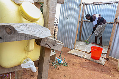 Ahmed Hussein disinfects the family latrine, a critical step that helps prevent disease. Photo by Sara A. Fajardo/CRS