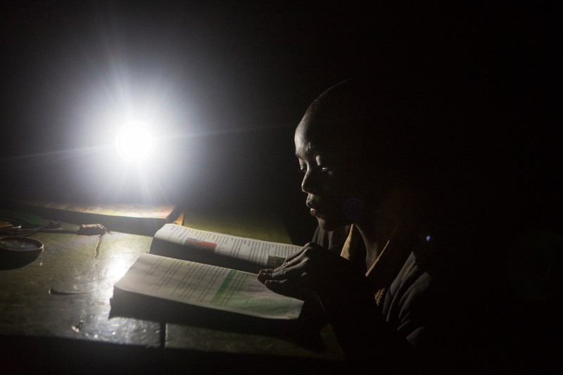 Levis studies by the light of a solar lamp late into the night. Felix saved his money to give his brother this luxury and help him succeed in school. Photo by Sara A. Fajardo/CRS