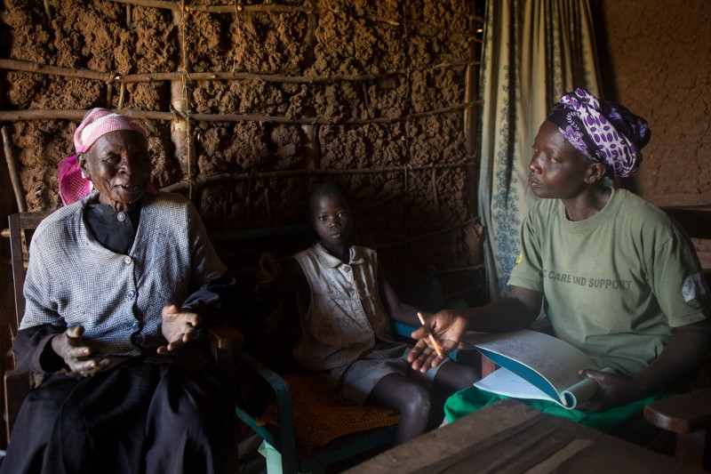 Fleria Chuka, left, cares for her grandson, Evans, orphaned by the AIDS epidemic in Africa. She welcomes the counsel and friendship of CRS volunteer health worker Mary Atieno Onyango. Fleria lost four of her five sons to AIDS. Photo by Sara A. Fajardo/CRS