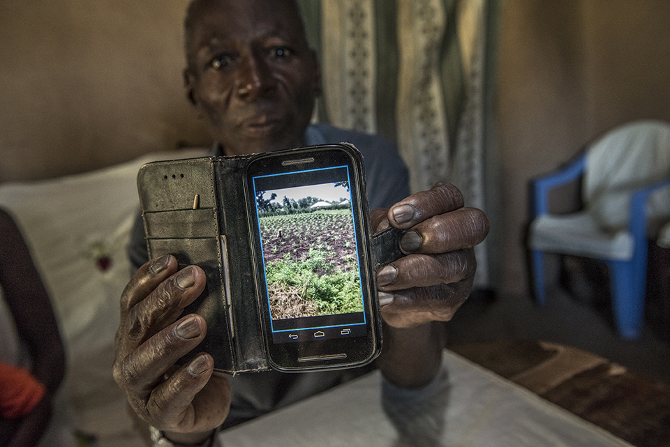 Kenya farmer shows picture of land