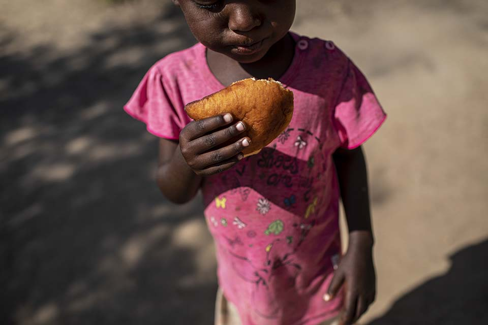 Kenya girl eats pastry called mandazi