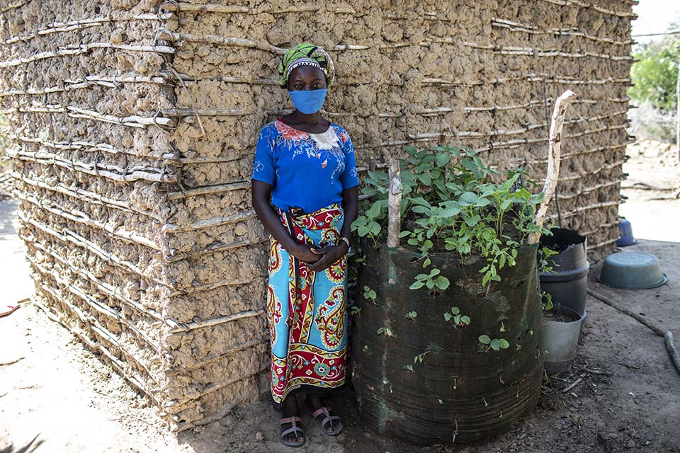 Kenya woman stands outside her home near her small garden