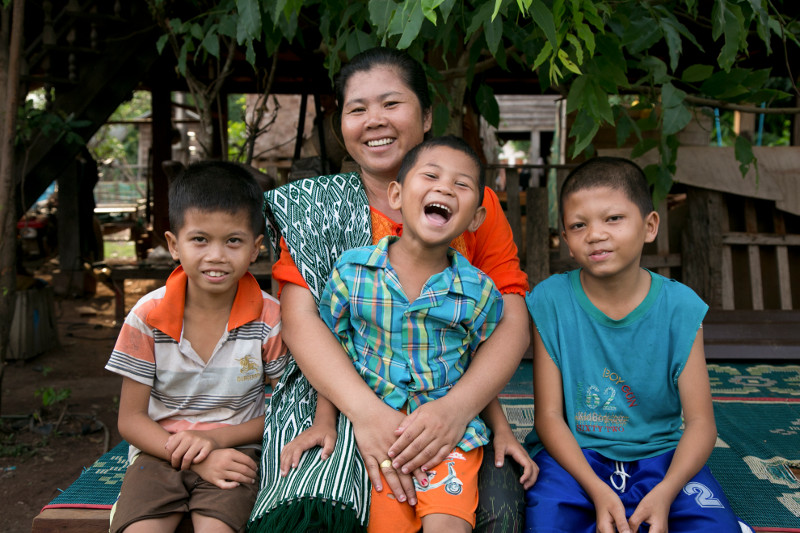 Hongkham Phengsaphone, of Laos, with three of her sons. The boys receive school lunches through a CRS program Hongkham participates in as a volunteer. You can read more about our work in Laos through CRS Rice Bowl.