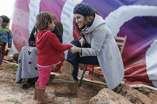 CRS Lebanon project manager Soha Menassa talks with a Syrian refugee from Raqqa in a tent-settlement in in Lebanon's Bekaa Valley. Photo by Sam Tarling for CRS