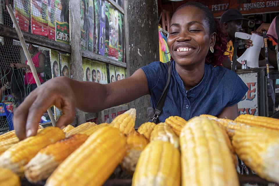 Liberian woman at market selling corn