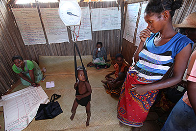A health worker weighs children in Mahatsara, Madagascar, each month to monitor their growth. Photo by Sara A. Fajardo/CRS