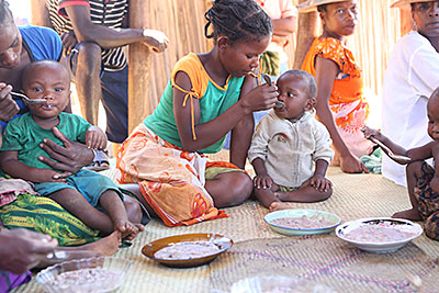 A mother in Madagascar feeds her daughter peanut stew. She learned to make it at a CRS-sponsored nutrition session during which children received 12 days of high-fat, high-protein food. Photo by Sara A. Fajardo/CRS