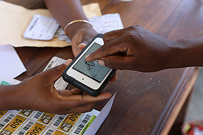 A farmer in Madagascar signs her name on the touch screen of an iPod before receiving barcoded vouchers that she'll use to purchase seeds for planting. Photo by Sara A. Fajardo/CRS