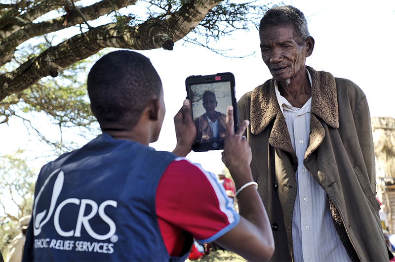 CRS field staff register beneficiaries for programs using mobile devices.