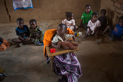 CRS helped provide Promisi a special chair so she can attend classes at the child care center in Nsanama Village, Malawi.