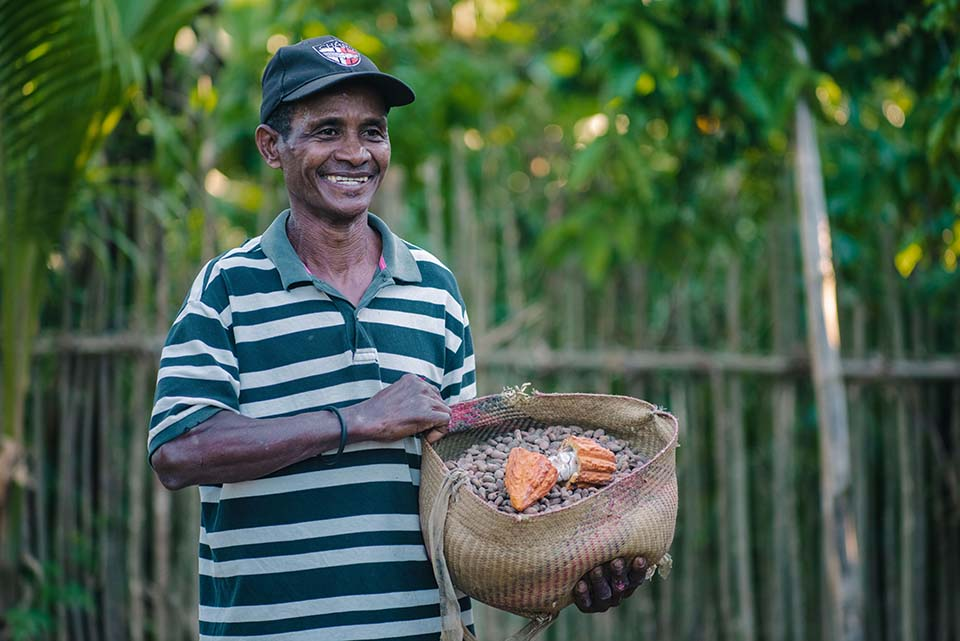 smiling Malagasy man holds basket full of cacao beans