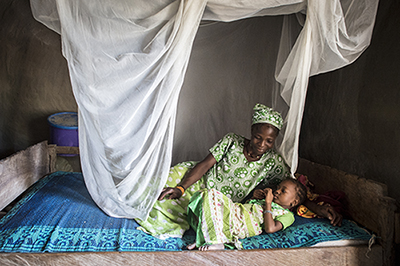 mother and child under malaria net