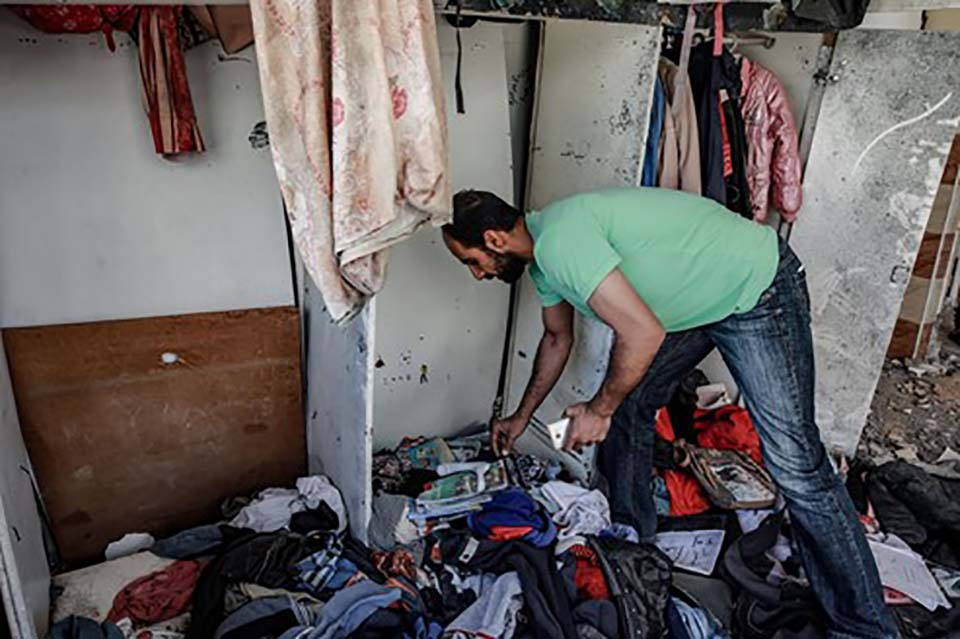 man stands removes belongs from a home destroyed in Gaza