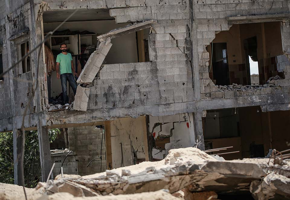 man stands in remains of home destroyed in Gaza