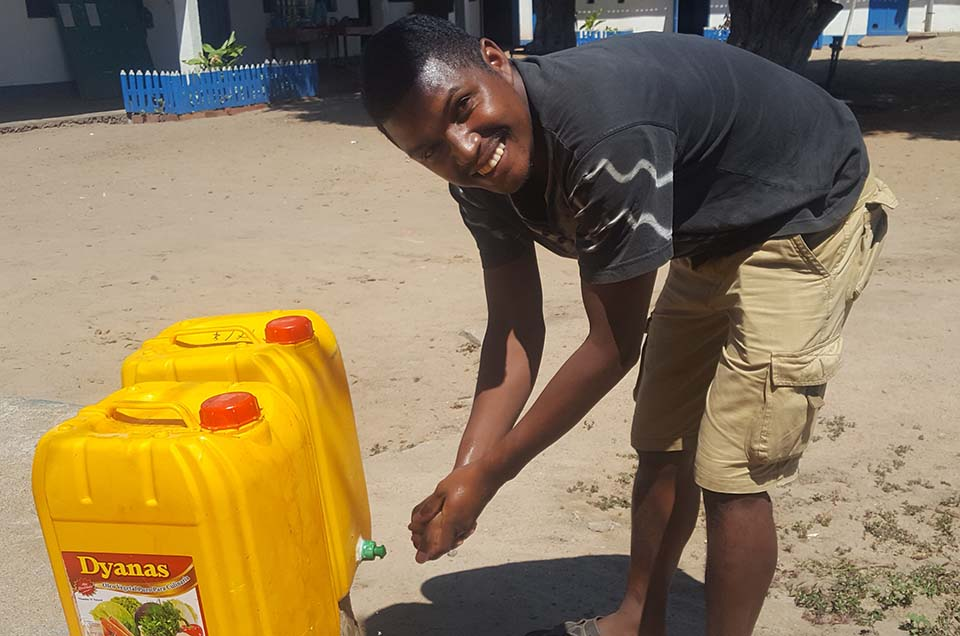 man washes his hands with water from a jerry can in Madagascar