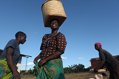 At an upcoming wedding for her niece, Mary Kamangeni, center, will serve the sundried corn she's carrying from her fields in Malawi. Her crops are thriving because of the new agricultural techniques taught in a CRS project. Photo by Sara A. Fajardo/CRS