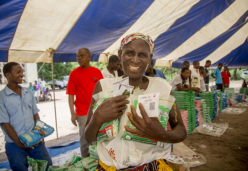 Alefa Tom receives drought-resistant seeds at a CRS-supported seed fair in Malawi.