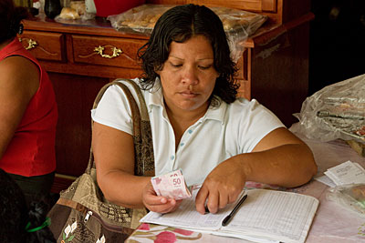 A woman counts money at a Bancomunidad meeting. The program, coordinated by a CRS partner in Mexico, enables women to become financially stable so they can help support their families. Photo by Philip Laubner/CRS