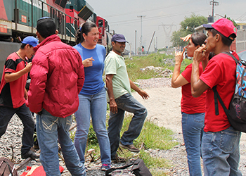 Migrants gather near a train often used as transportation through Mexico.  Photo by Christian Melendez Lopez/CRS