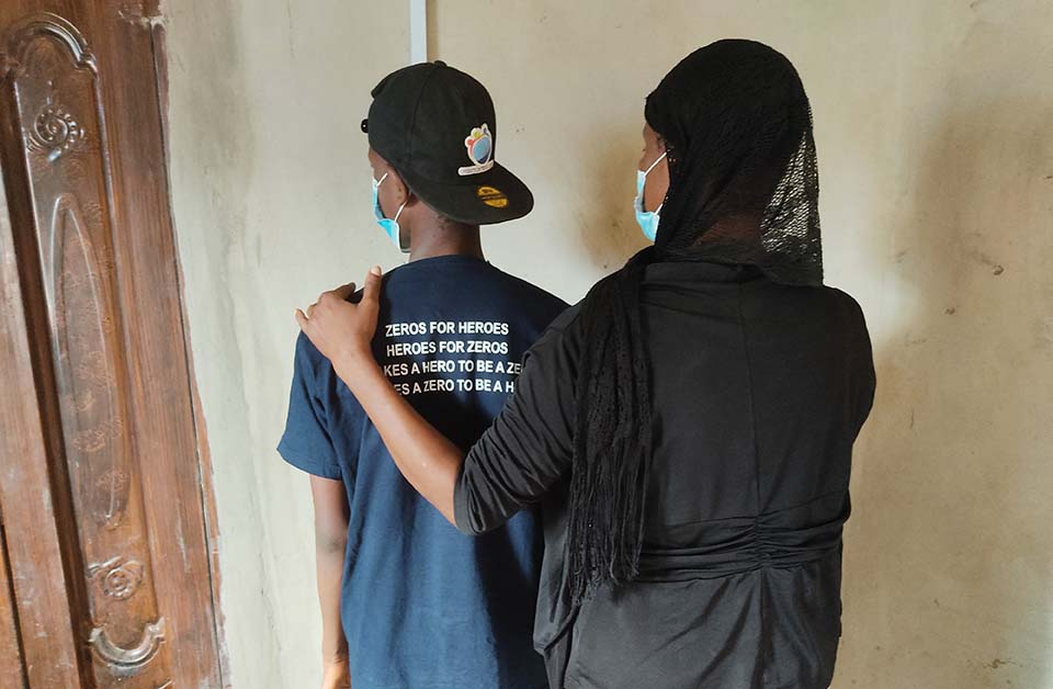 mother with hand on sons shoulder with their backs to camera