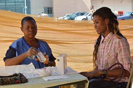 CRS volunteer Ngozi Ifediagwu, left, teaches people about HIV and AIDS, and tests them for the virus. Photo by George Akor/CRS