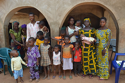 Nwoba Ogbonna, holding infant in front row, with adults and children she helped deliver. Photo by George Akor/CRS