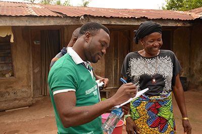 Segun Owoyermi, CRS program manager for the Sustainable Cassava Seed System project in Nigeria, works with Mwuese Jato, a farmer and a widow who heads a 14-member household. Photo by Michael Stulman/CRS