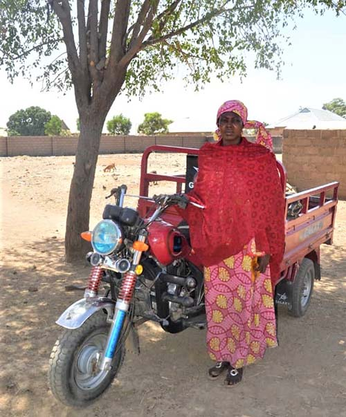 Nigerian woman standing near her motorized tricycle.
