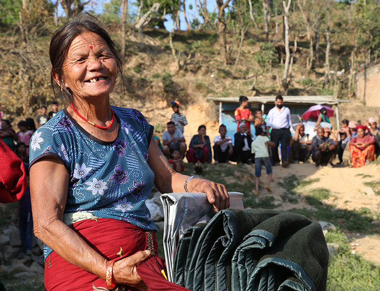 Kanchi Rama ties a tarp, blankets and sleeping mats together to carry to the ruins of her home in Gorkha district. Photo by Jennifer Hardy/CRS