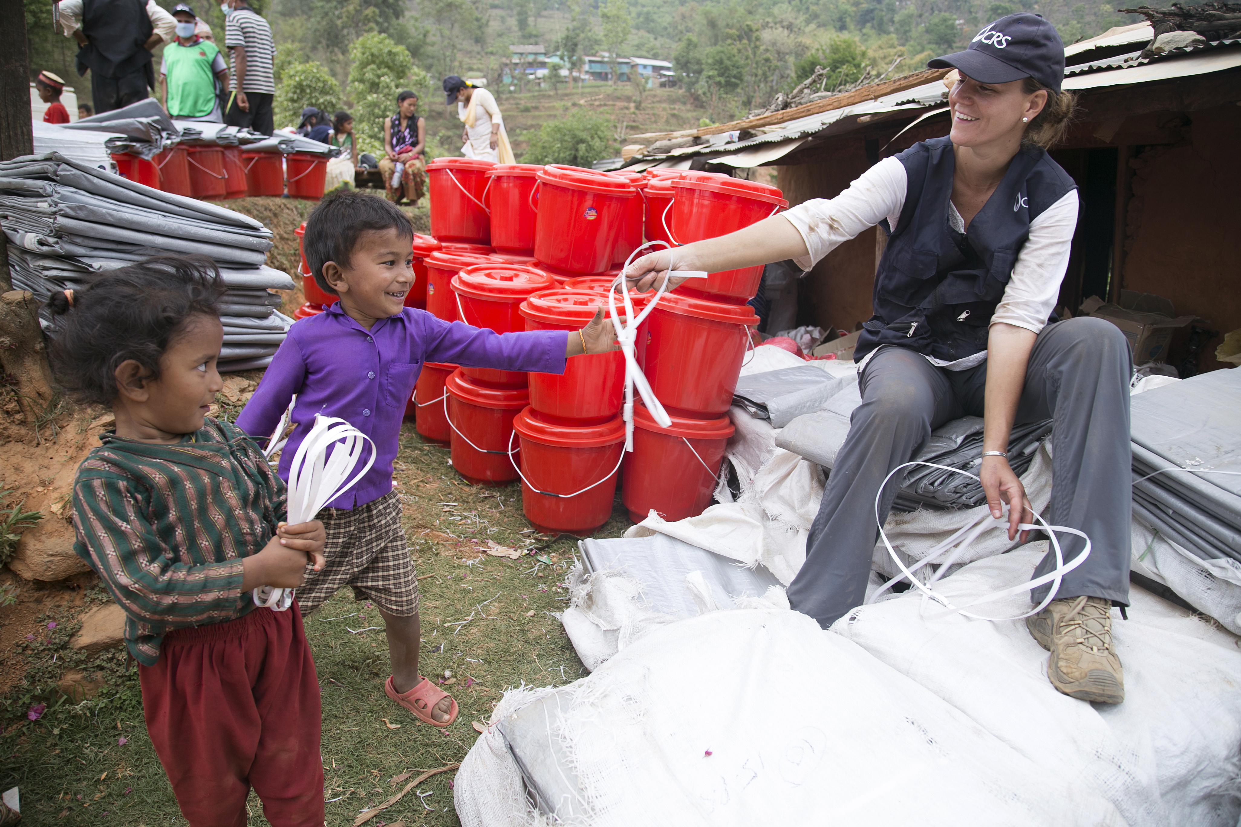 CRS staff member Elizabeth Tromans unpacks supplies for a distribution in Nepal, where we've provided items such as hygiene kits, like those in the background, to 103,000 people. Photo by Jennifer Hardy/CRS