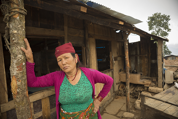 Kumari Gurung outside her family's shelter last year. With supplies and a grant from CRS, the Gurung family has constructed a temporary hotel, while they raise money to rebuild their former hotel. Photo by Jake Lyell for CRS