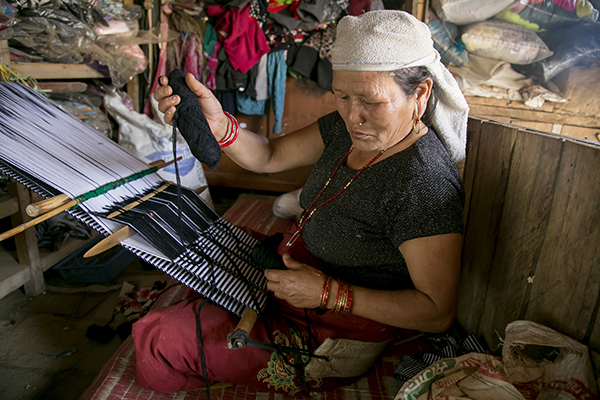 Kumari Gurung weaves handmade bags neighbors buy for their children's schoolbooks. It's one way she is earning money to rebuild her hotel. Photo by Jennifer Hardy/CRS