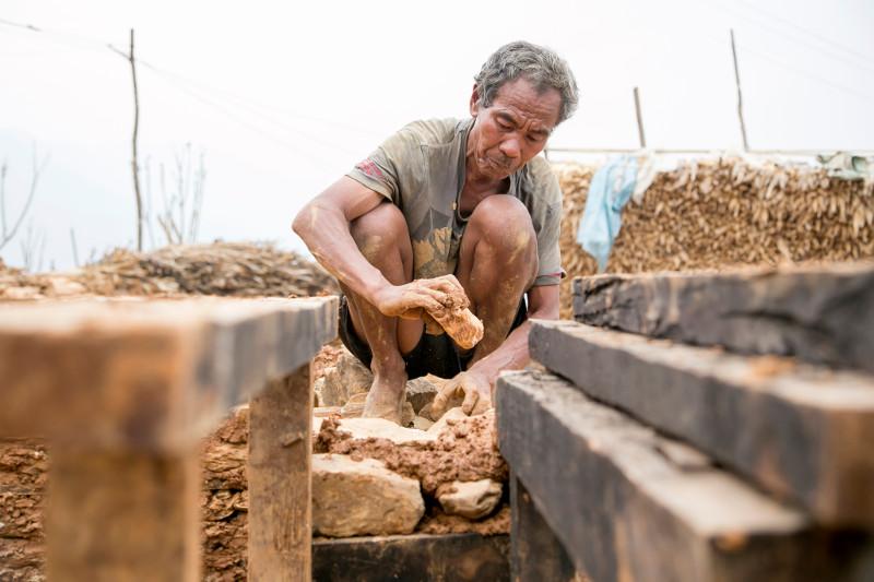 Dal Bahadur Rana Magar is learning earthquake-resistant construction methods, working under the supervision of CRS-trained mason Jyam Bahadur Thapa Magar.