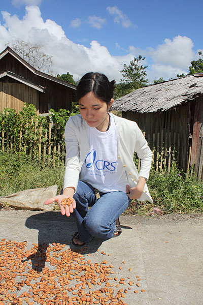 CRS staffer Dina Fortich examines cacao beans drying on a surface paved by a USDA-CRS program. Small farmers often do not have enough space to dry their beans. Photo by Laura Sheahen/CRS