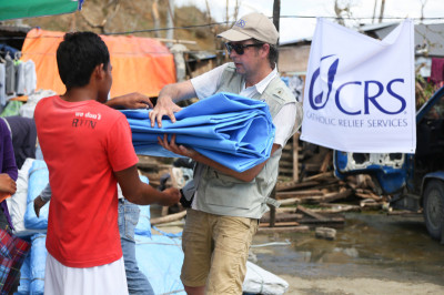 CRS staffer Ross Tomlinson hands out plastic tarps at a CRS and Caritas Norway distribution of 700 emergency shelters in central Philippines. The area was struck by Typhoon Haiyan on November 8, 2013. Jim Stipe/CRS