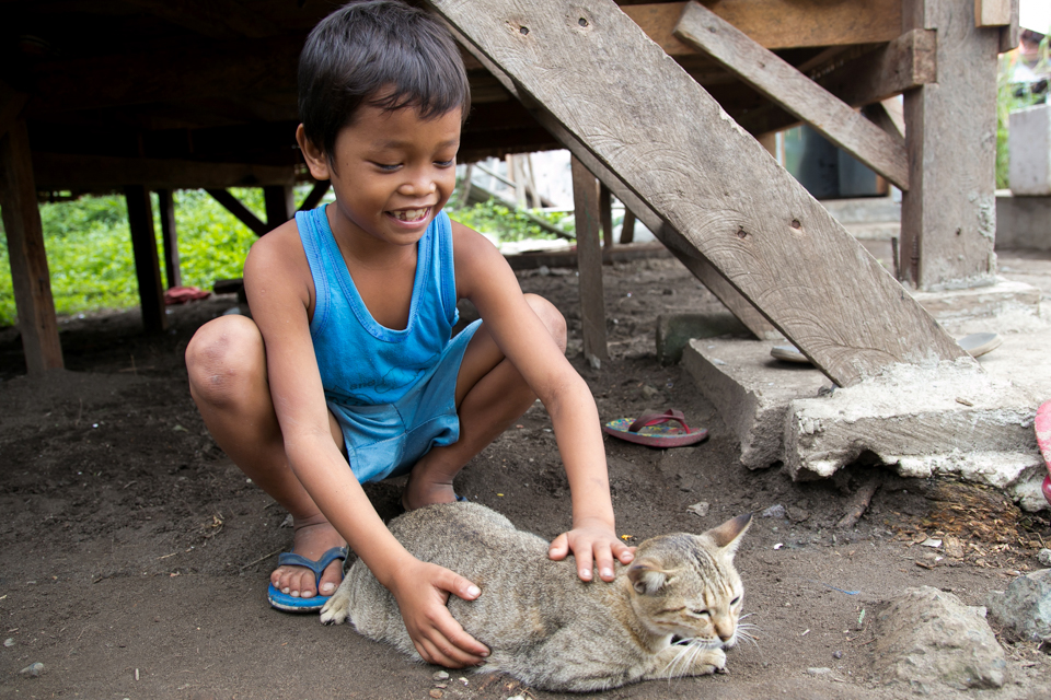 boy pets cat in the Philippines