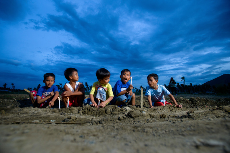 Children in the Philippines light candles during a house blessing for people impacted by Typhoon Haiyan. Photo by Charlie David Martinez for CRS