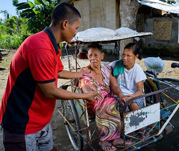 Ric De Veyra helps Florencia Lluviso exit his bicycle rickshaw, assisted by Velma Lluviso, daughter of Florencia. De Veyra helped his entire community during recovery from Typhoon Haiyan. Charlie David Martinez for CRS