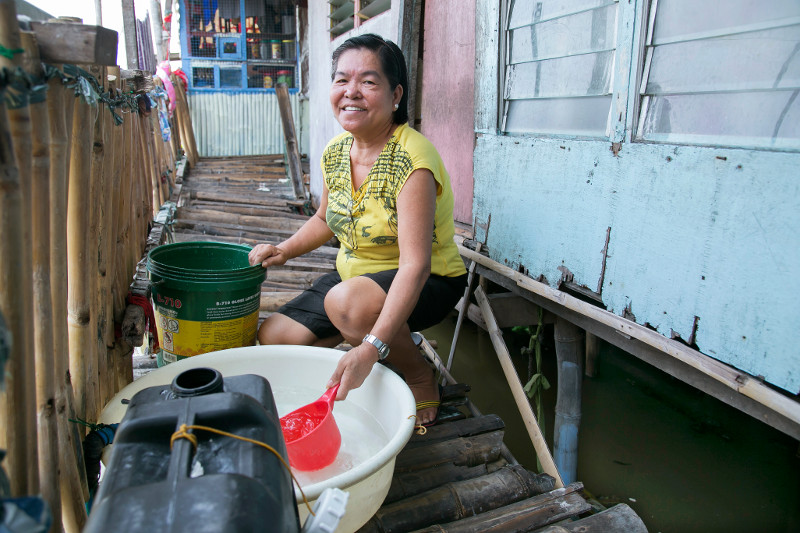 Rebecca Macaraig Yumang does chores in front of her home, which she has had to raise on stilts in recent years because of rising water in the Philippines. Photo by Jennifer Hardy/CRS