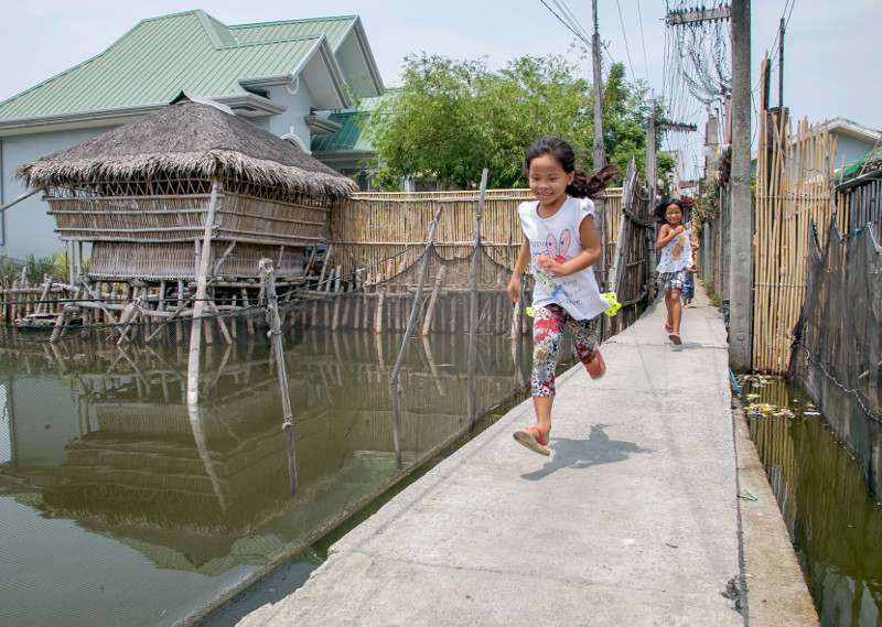 Girls run from a main road into a flooded neighborhood in the Philippines. Before CRS began working with communities to organize monthly cleanups, these waterways were clogged with garbage. Photo by Jennifer Hardy/CRS